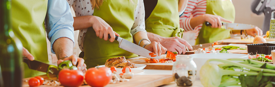 Four people cutting vegetables in a cooking class.